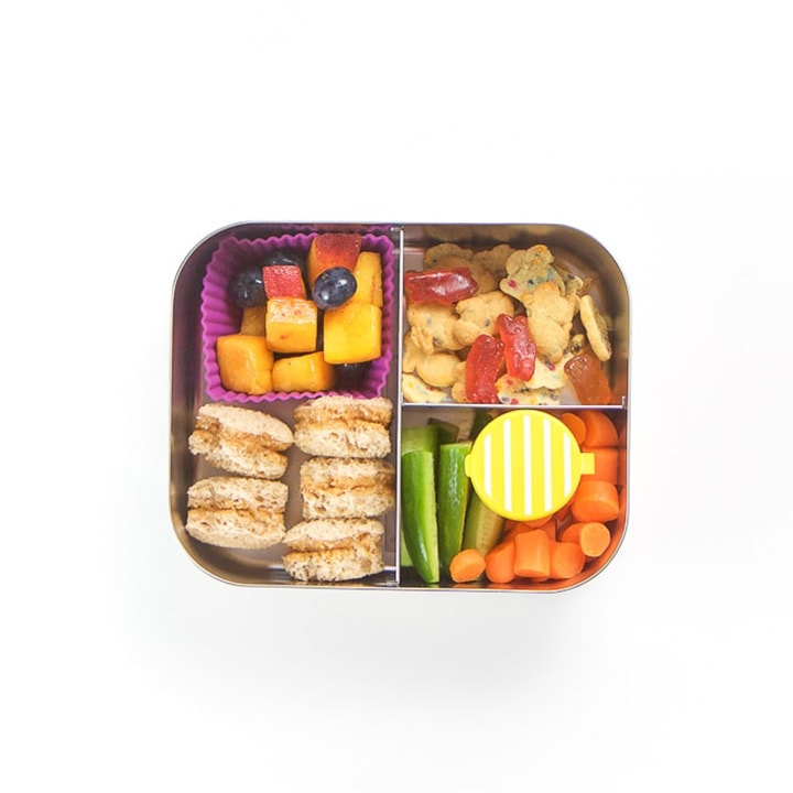 School lunch box with lids on a counter - full of a healthy lunch.