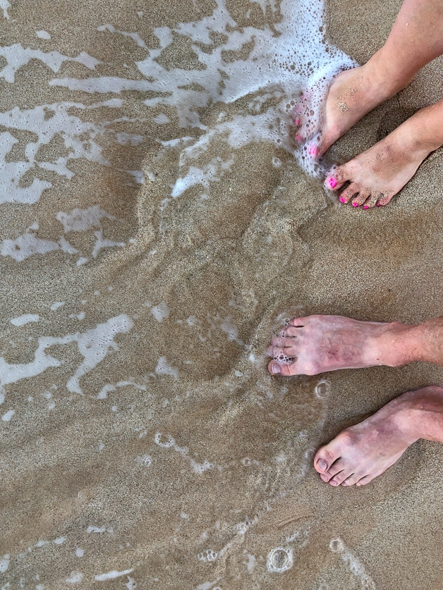 Feet in the sand by the ocean.