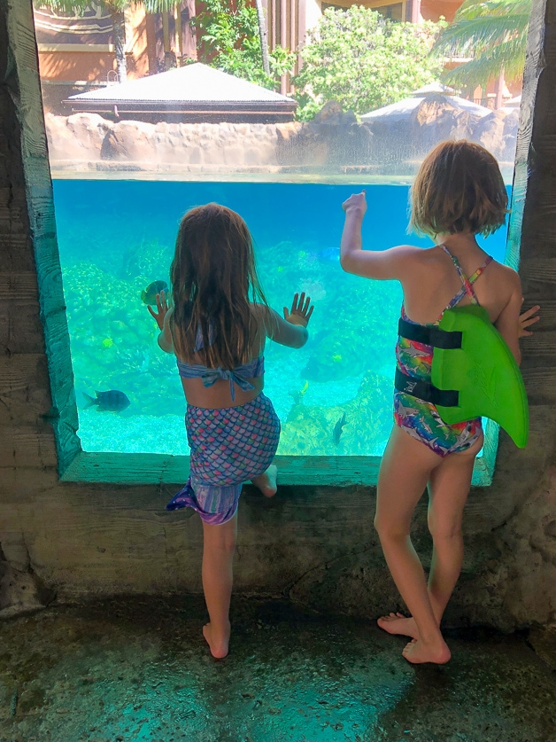 two girls standing by the fish tank at Disney Aulani.