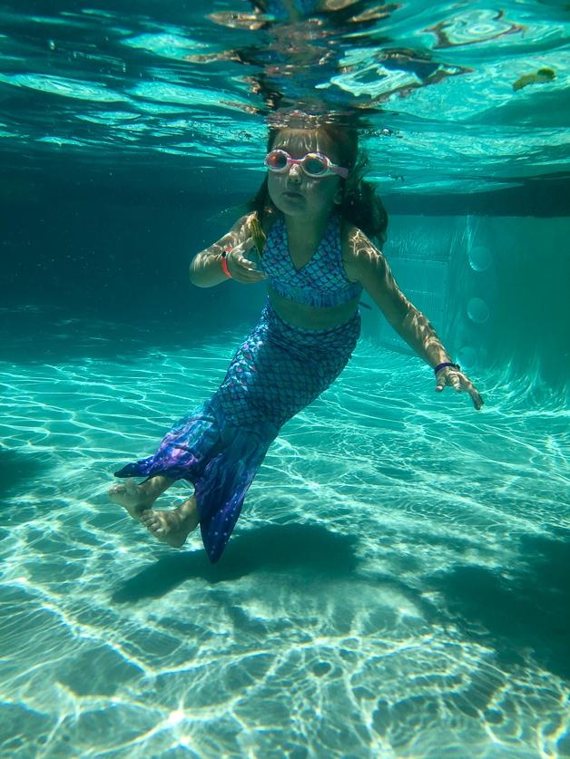 Girl swimming in pool at Disney Aulani.