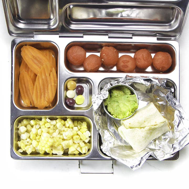 A bento box filled with burritos, watermelon, carrots and popcorn.