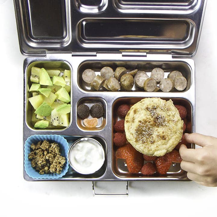A fun lunch box for kids that has leftover muffins and healthy foods inside.