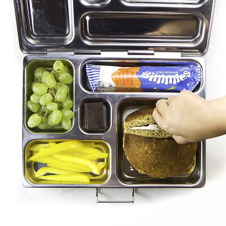 A packed lunch box with healthy pancakes, veggies and fruit.