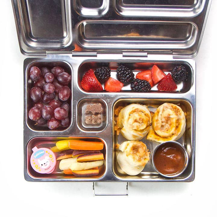 A fun school lunch box for kids that is packed with food.