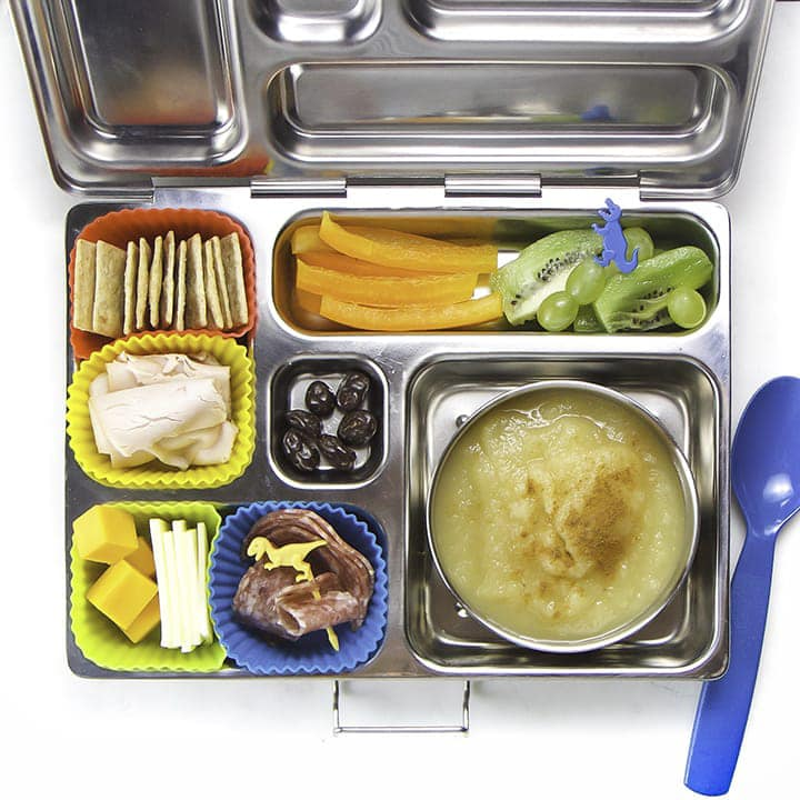 A silver bento box packed with healthy foods for kids.
