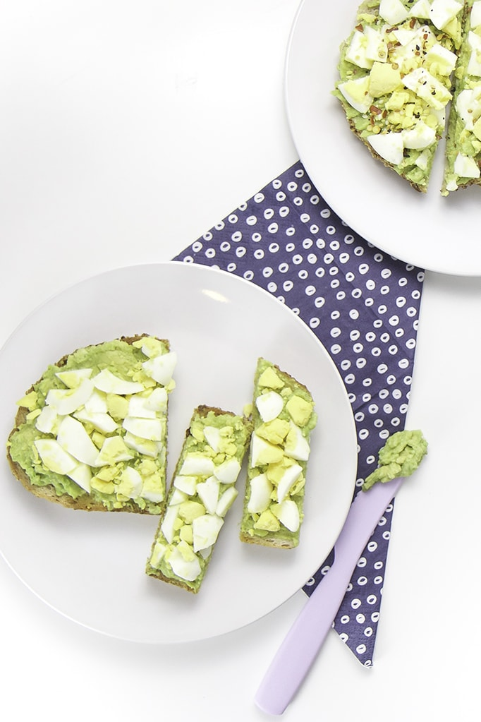 Two round white plates both filled with avocado and egg toast - one for baby and one for you.