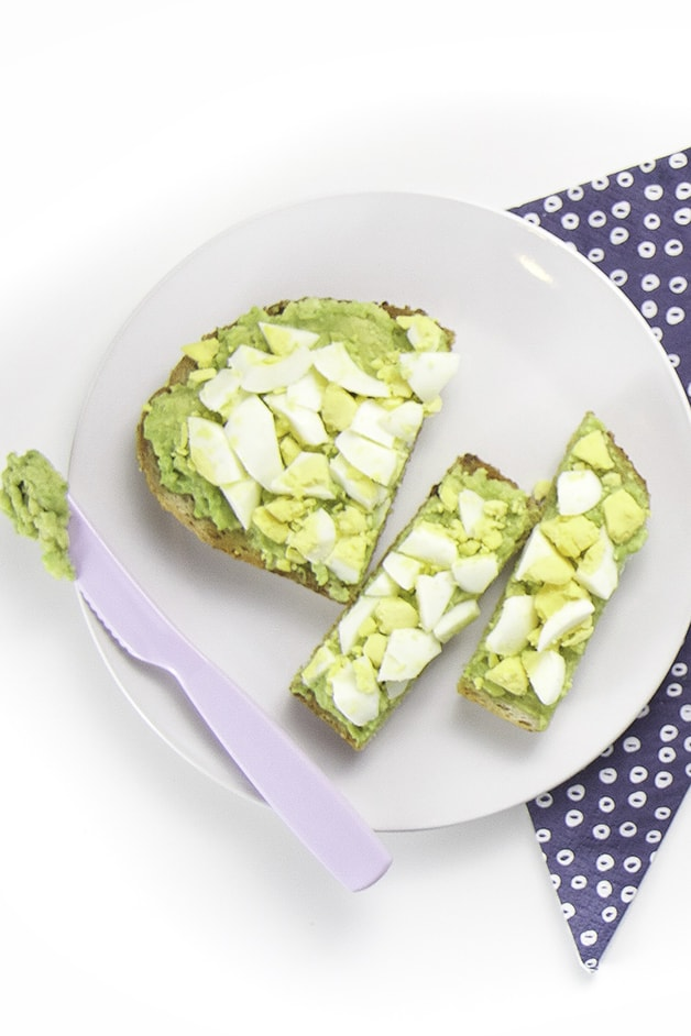 Round white plate with a cut up avocado and egg toast for baby + toddler.