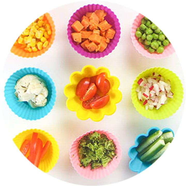 grid of silicon muffin liners with baby-led weaning finger foods inside.