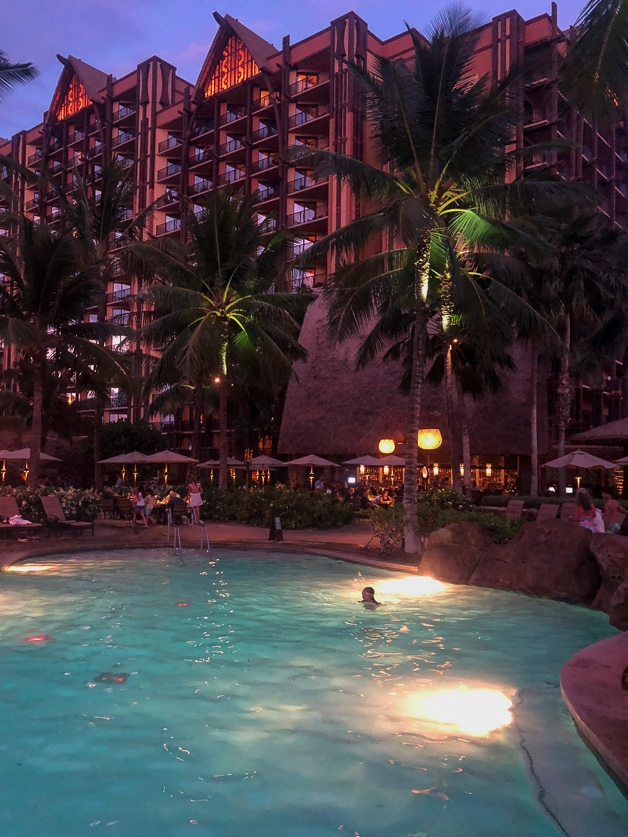 Girls swimming in pool at night with Disney Aulani behind her - best of.