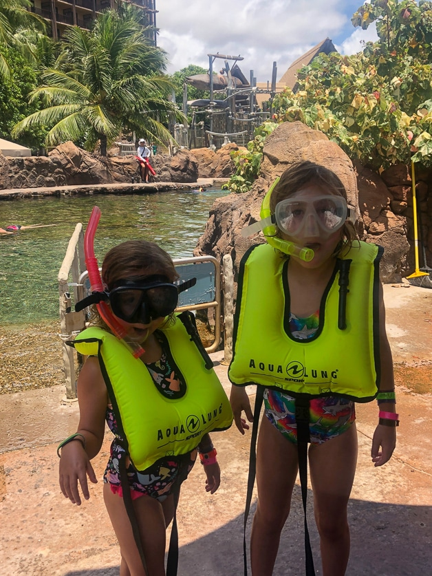 2 girls with diving gear on getting ready to snorkel.