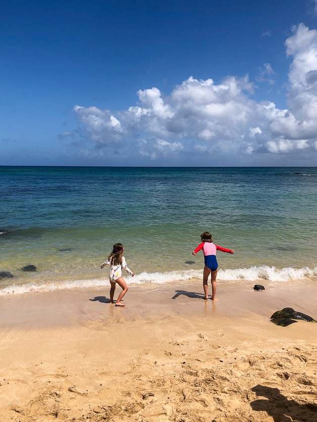 two girls play by the ocean, looking for turtles.