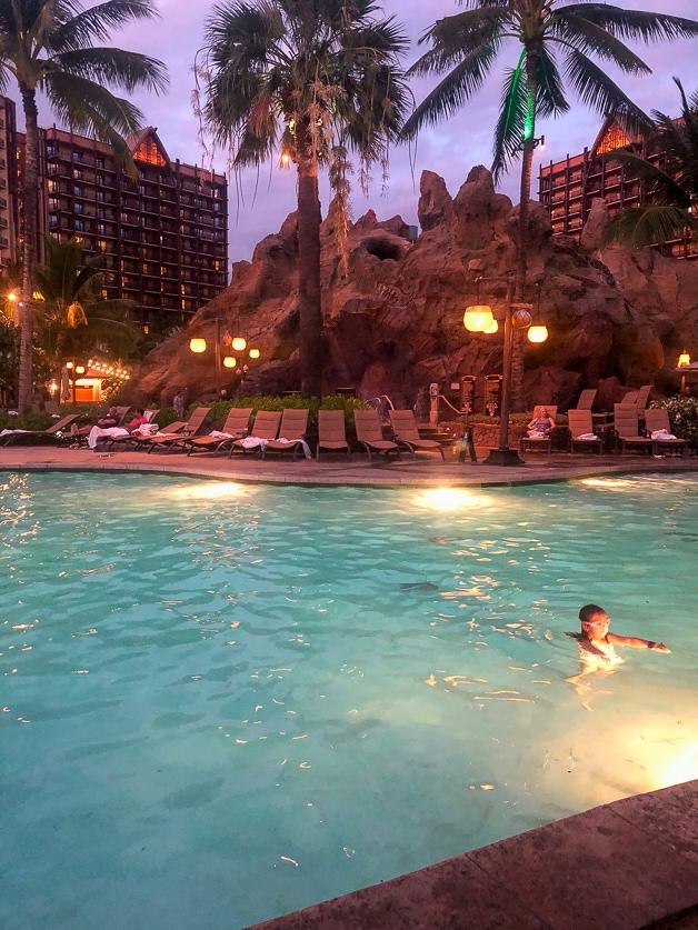 Girl swimming in pool at night - best Disney Aulani Resort.