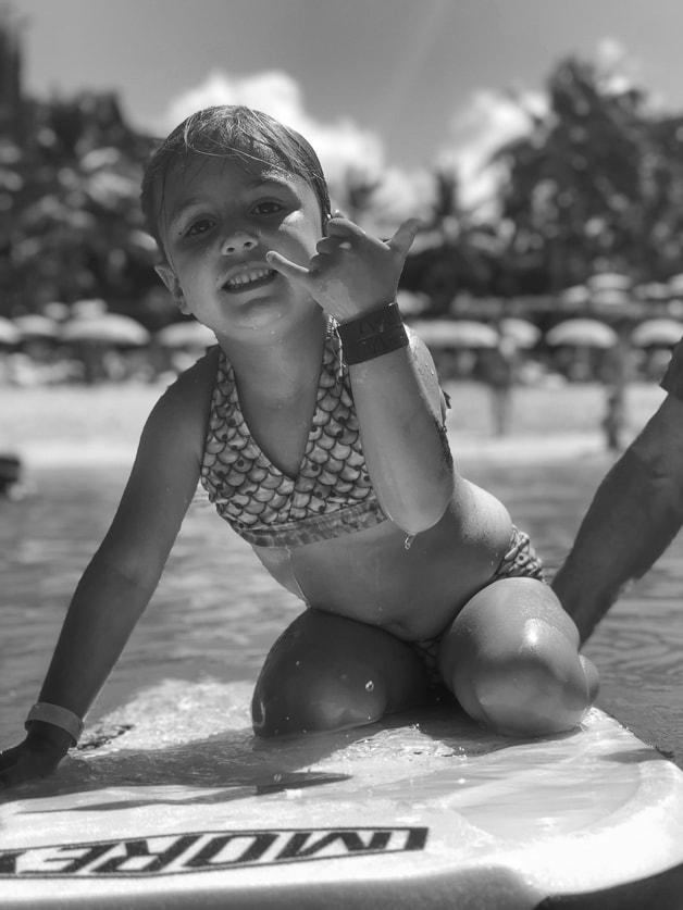 Girl on boogie board in lagoon by Disney Aluani.