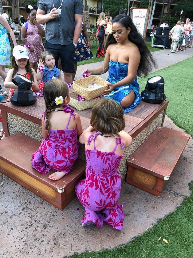 Girls making leis at the la'ua - best at Disney Aulani.