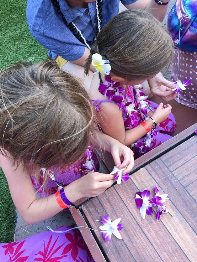 unclose of girls making leis.