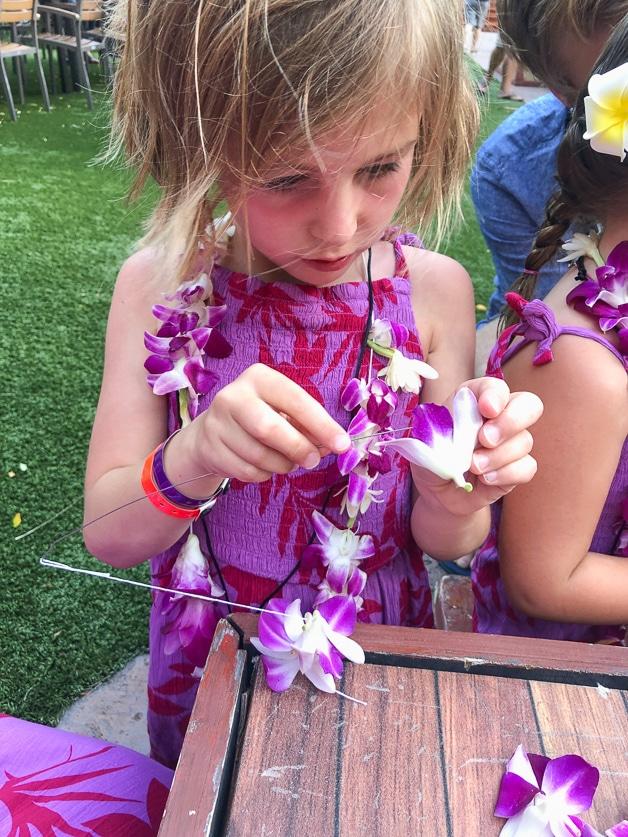 girl making purple lei.