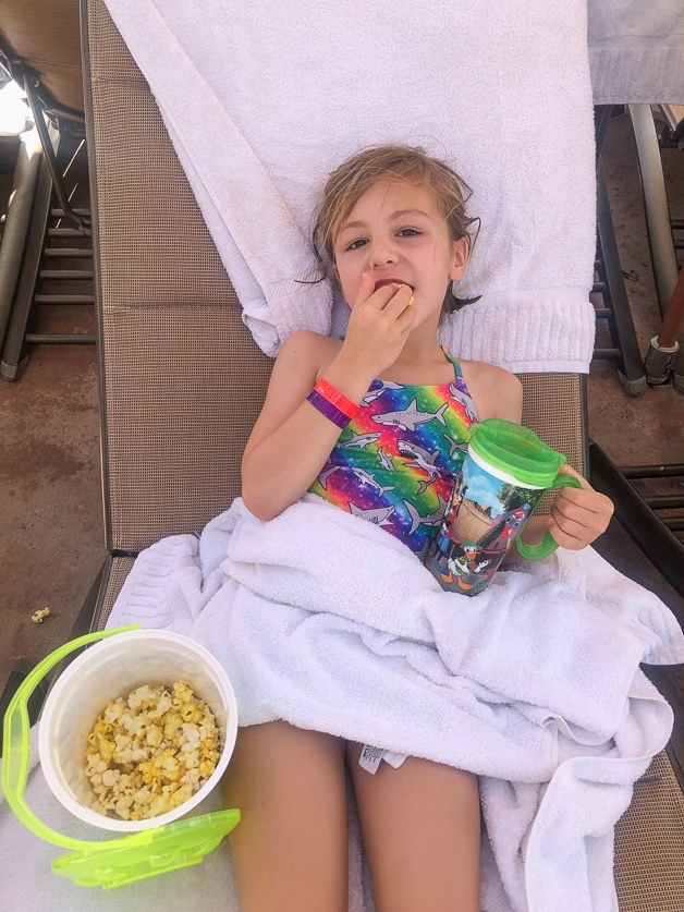 Girl living best life with a bucket of popcorn and lemonade.