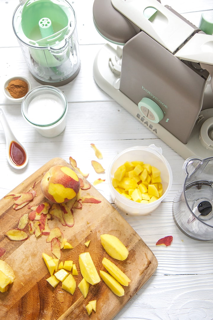 A Beaba baby food making machine is surrounded by peaches and other produce to make this recipe.