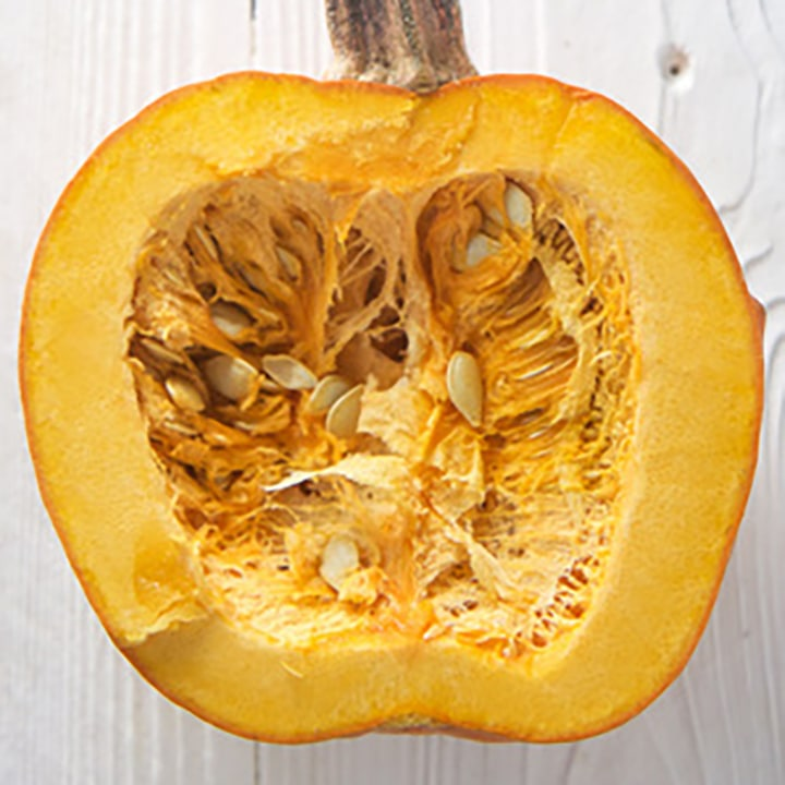 small pumpkin sliced open with the seeds in it.