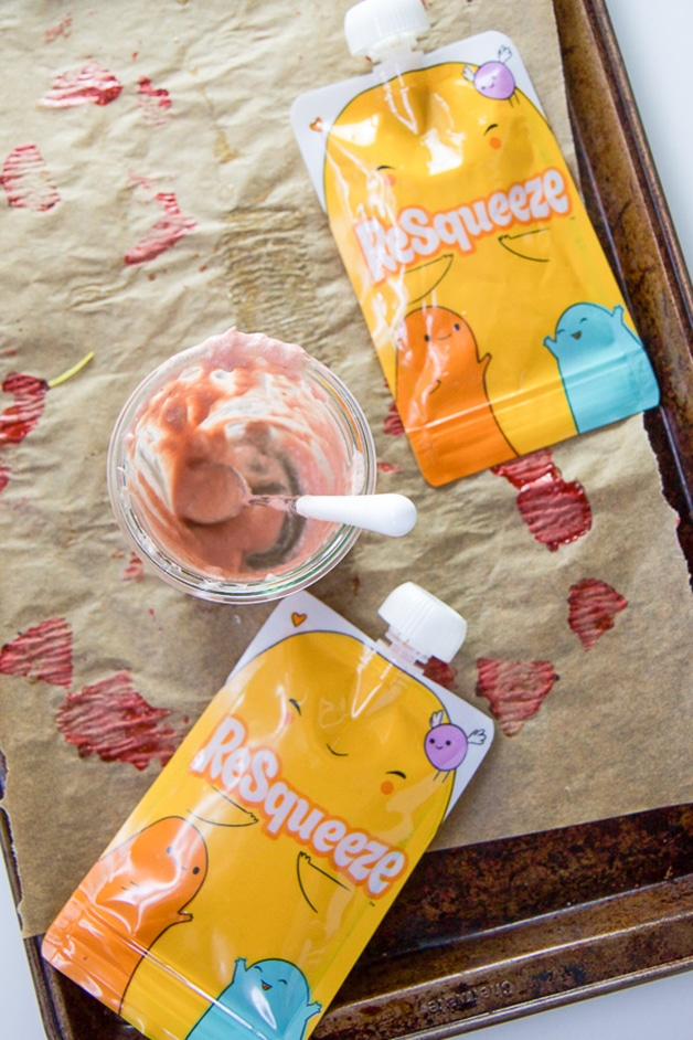 A baking try with a clean glass jar of baby food and 2 reusable baby food pouches.