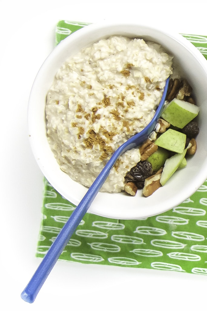 One white bowl filled with thick oats with a sprinkle of cinnamon on top. There is a spoon inside the oats showing the surprise toppings underneath the oats.