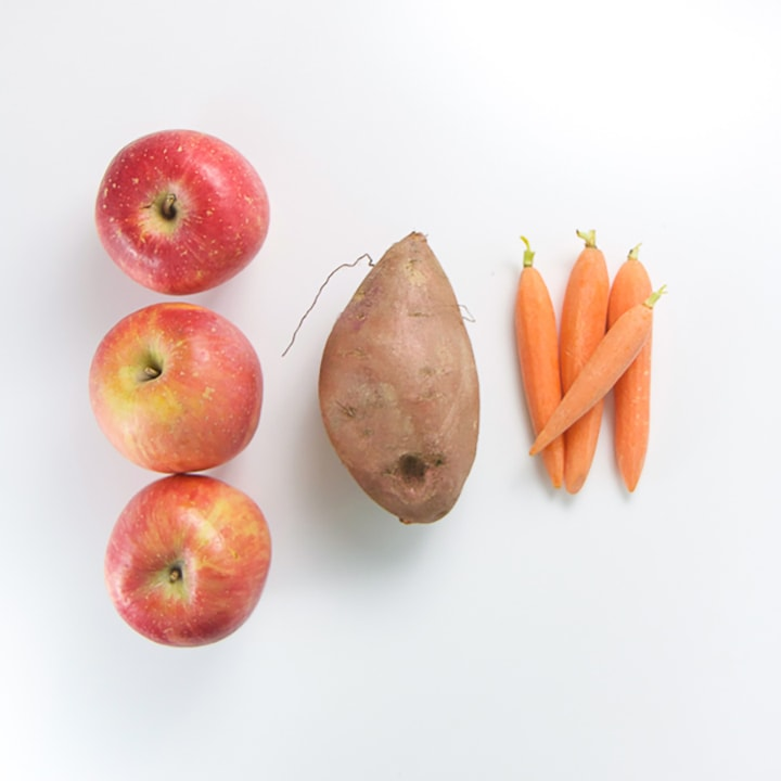 apple, sweet potato and carrots lined up on a white background.