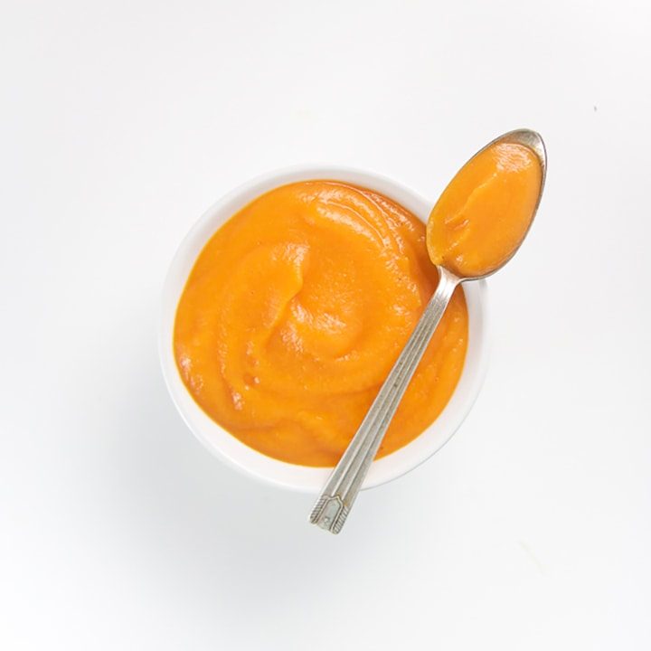 Small white bowl with spoon resting on top with homemade baby food puree inside.