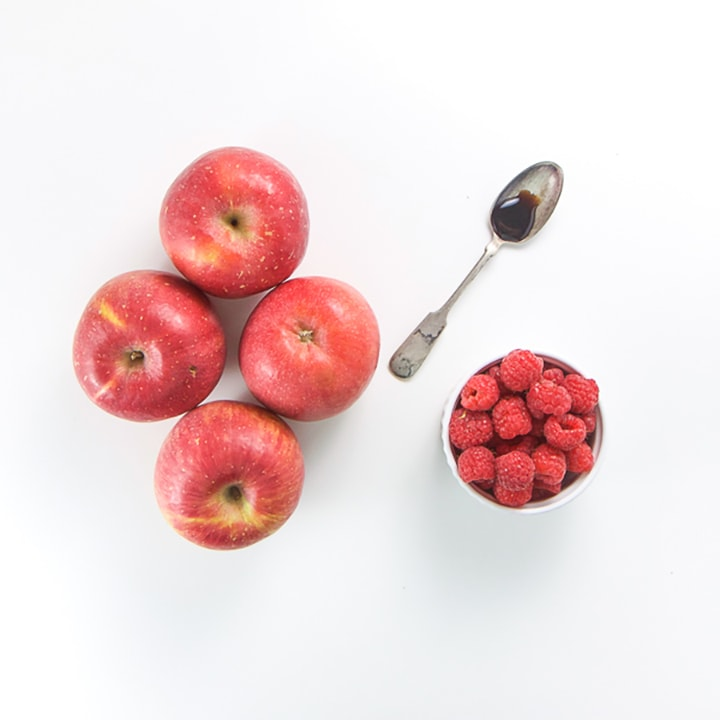 Apples, raspberries and a spoon full of vanilla scattered on a white background.