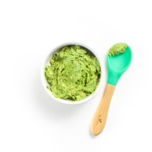 Smashed avocado in a small bowl with spoon resting next to it with puree on it.