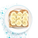 Almond Butter toast with bananas and hemp sprinkles sitting on a round plate.