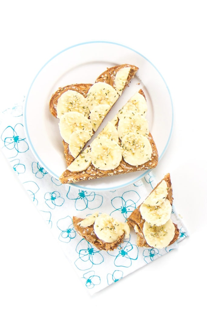 1 round plate with a sliced piece of almond toast for toddler with some torn pieces on a napkin below.