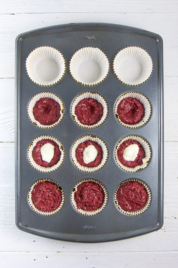 Muffin tray gettin full up of healthy beet chocolate muffins.