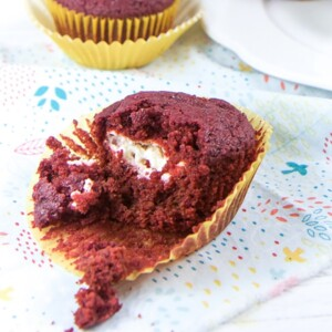 Beet muffin half way unwrapped sitting on a napkin.