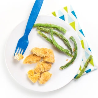 Round white plate with chicken nuggets and green beans on top. Fork resting on place with chicken on it.