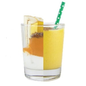 Clear cup cut in half, on one side is the ingredients for the smoothie, on the other side is the smoothie itself with a straw sticking out.