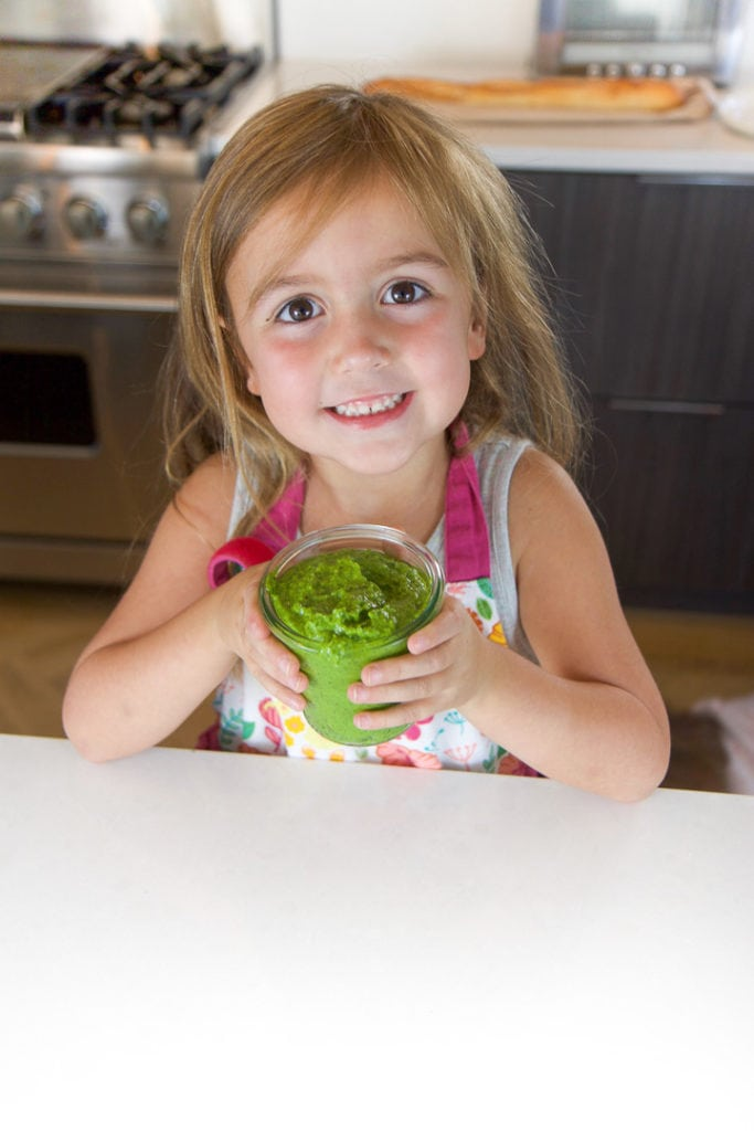 little kid in a kitchen, holding a jar of spinach basil pesto.