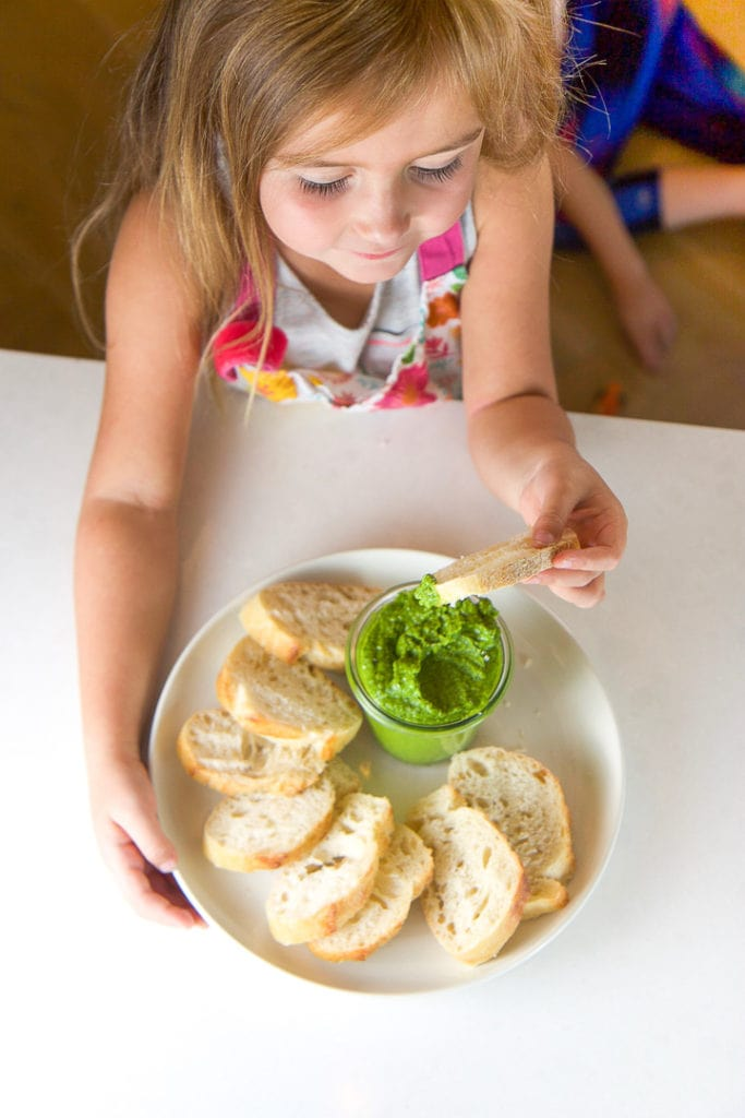 A girl dipping a piece of bread into the spinach basil pesto she made.
