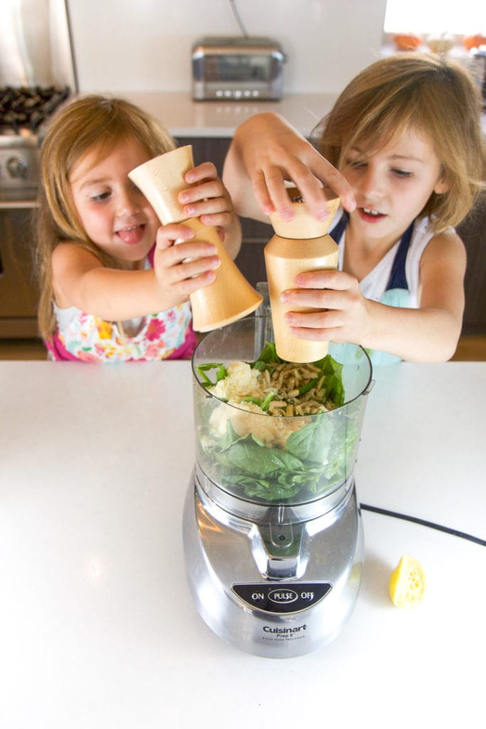 2 girls putting salt and pepper into a food processor.