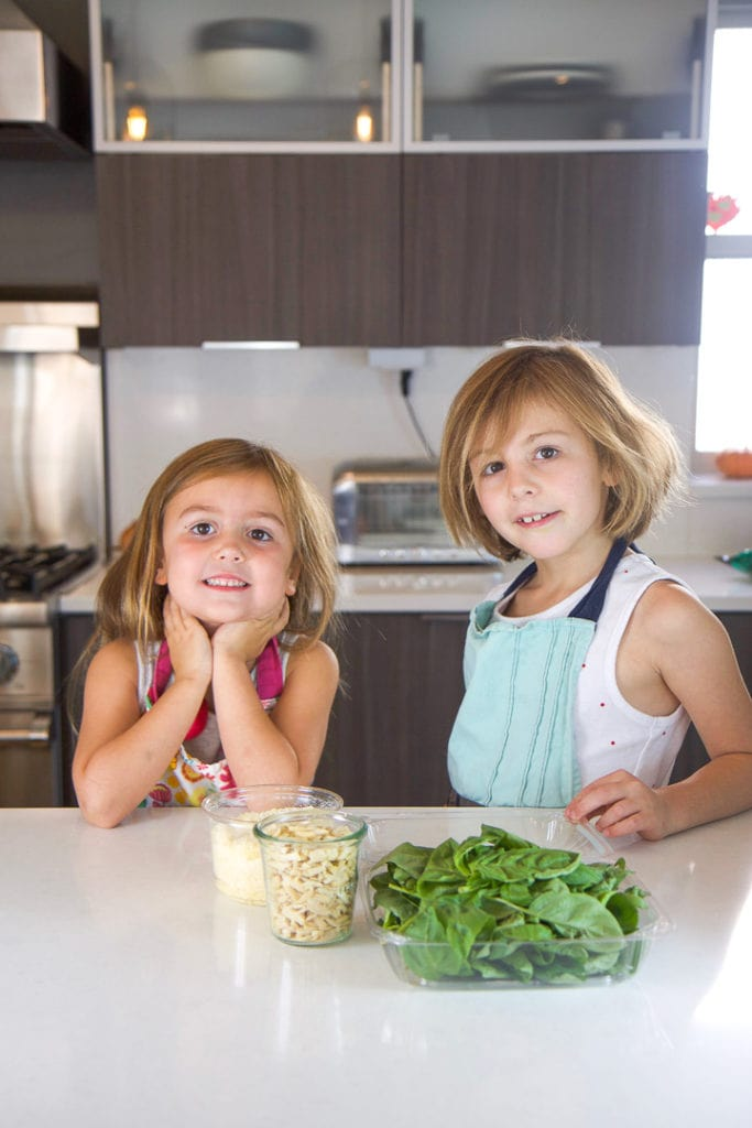 2 girls standing in a kitchen counter with a spread of recipe ingredients in front of them.