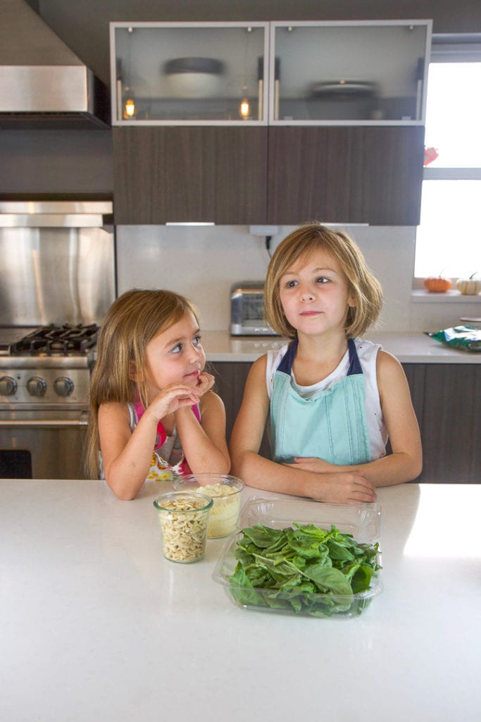 Cooking with kids - 2 girls standing in a kitchen counter with a spread of recipe ingredients in front of them.