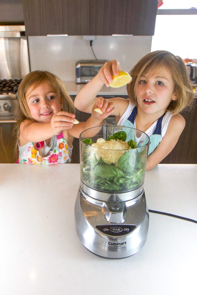 2 girls place items into a food processor - cooking with kids.