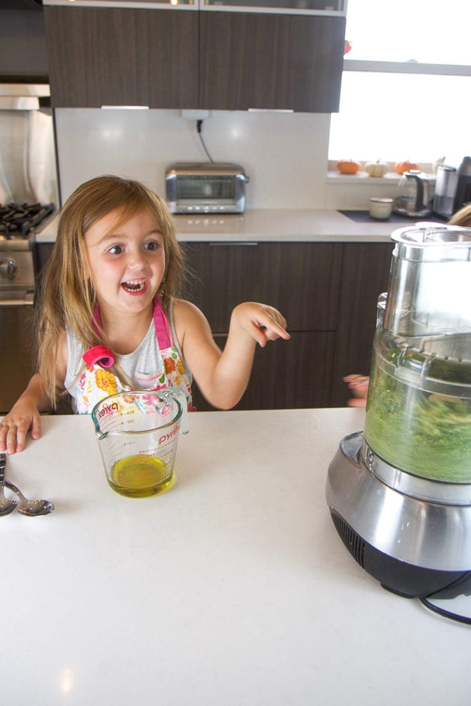 kids cooking in the kitchen - making a pesto recipe.