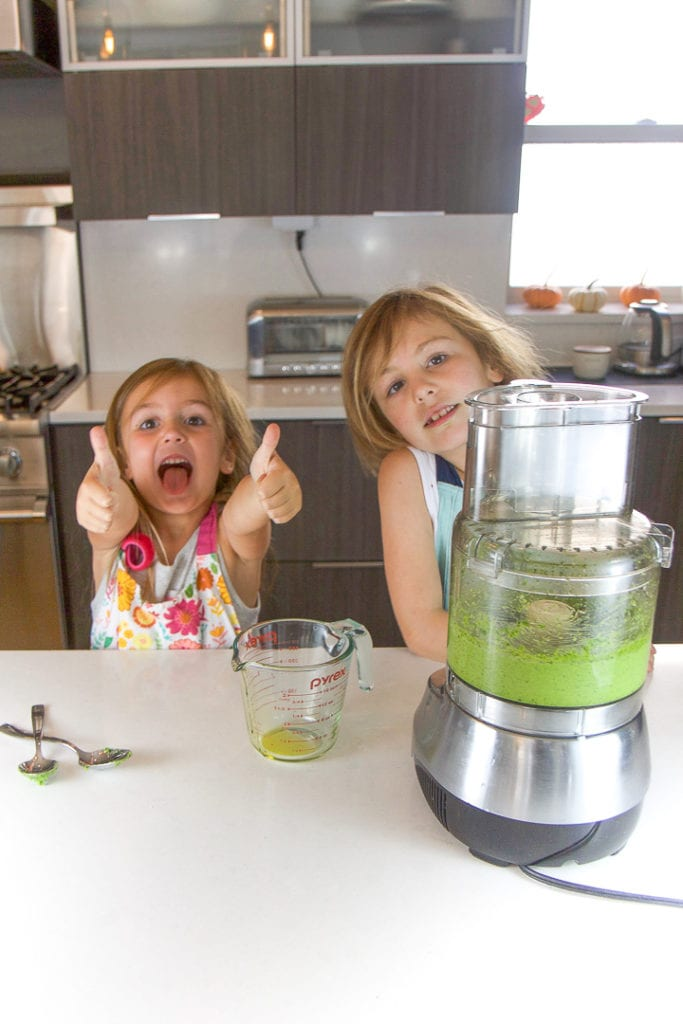 2 kids very excited about cooking in the kitchen.