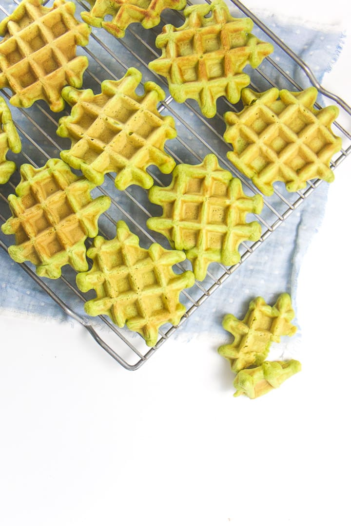 Spinach waffles sitting on a cooling rack.