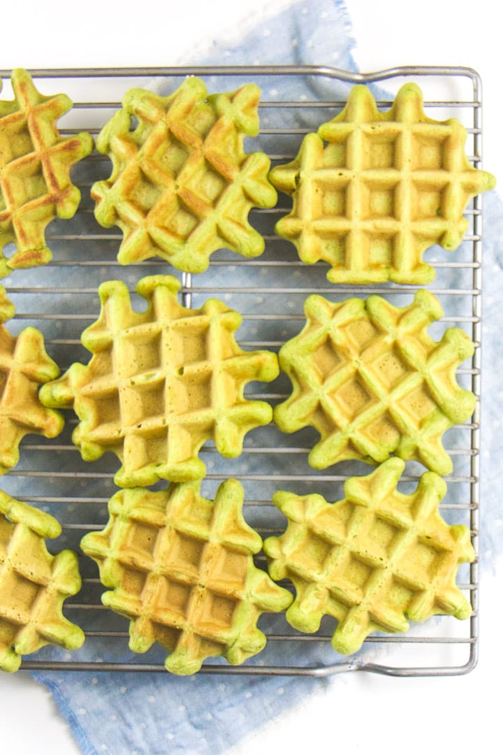 spinach waffles for baby and toddler sitting on a cooling rack.