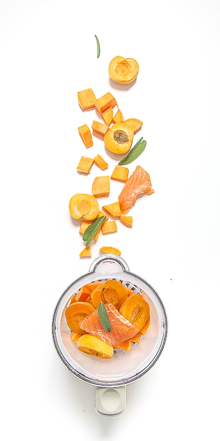 image is of a blender with produce scattered outside of it