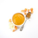 creamy and smooth bowlful of baby food puree with produce scattered around it.