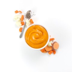 A small white bowl filled with creamy nutrient rich homemade baby food puree with produce around it.