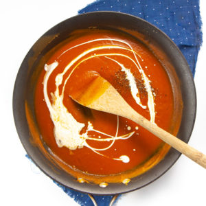 pumpkin sauce with a drizzle of cream in a skillet.