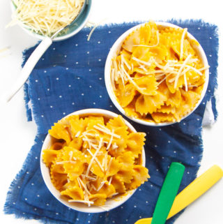 2 small bowls filled with pumpkin pasta with 2 kids forks on a blue napkin.